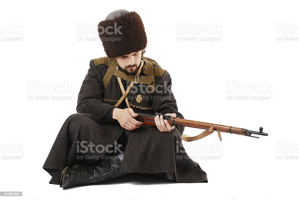 Russian Cossack inspecting a rifle in siitting position. stock photo