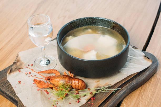 Russische Fischsuppe auf einem Holztablett in einem Restaurant, serviert mit gekochten Krebsen und einem Glas Wodka – Foto