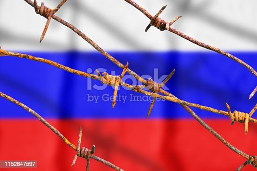 Russian flag behind rusty barbed wires with shadows. Symbol of violation of human rights in Russia
