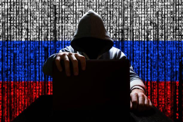 russische hacker sluit het deksel van de laptop, tegen de achtergrond van een binaire code, de kleur van de russische driekleur - rusland stockfoto's en -beelden
