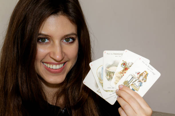 russian indoor girl with alice in wonderland playing card - whiteway alice in wonderland stock photos and pictures