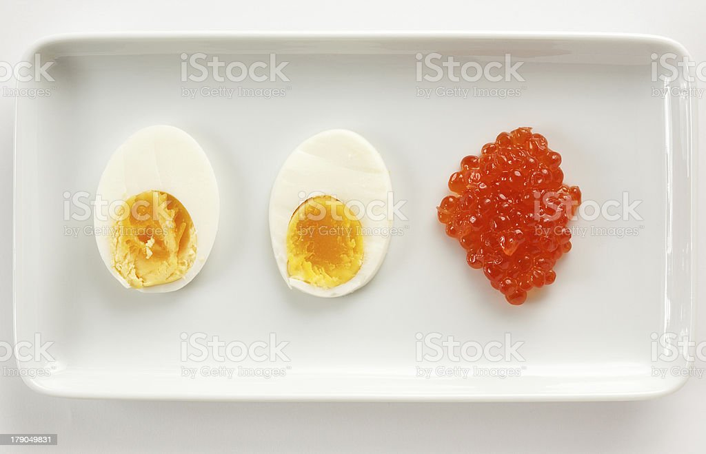 Russian keta / Japanese Ikura caviar with sliced organic egg. royalty-free stock photo
