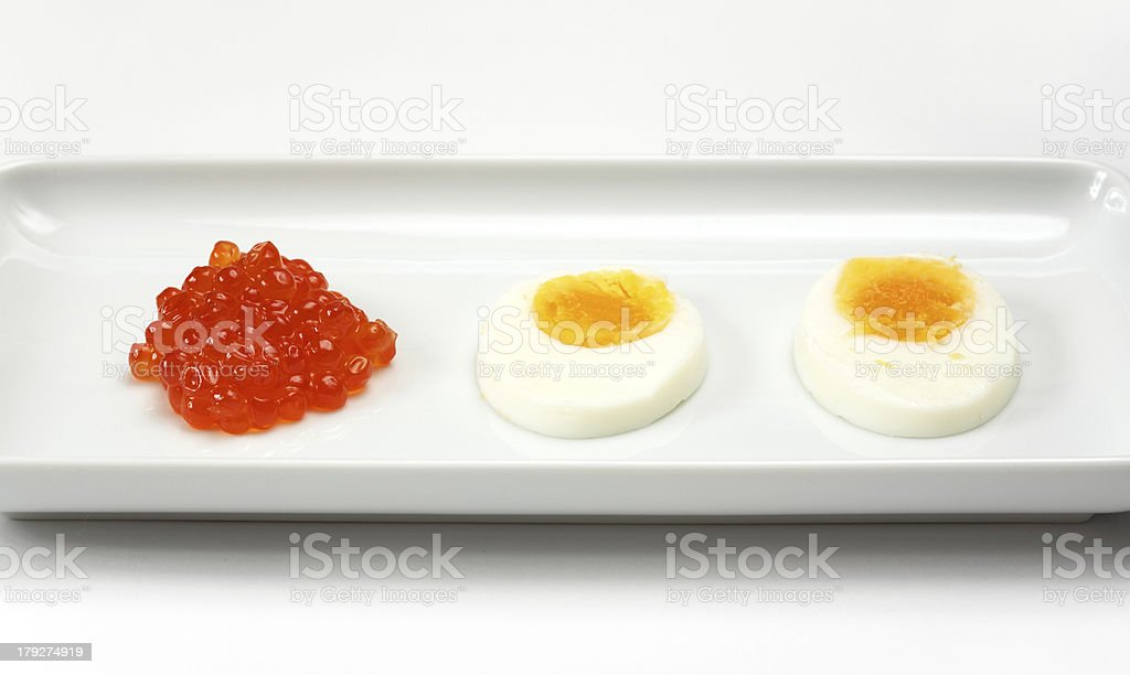 Russian keta / Japanese Ikura caviar with sliced organic egg royalty-free stock photo