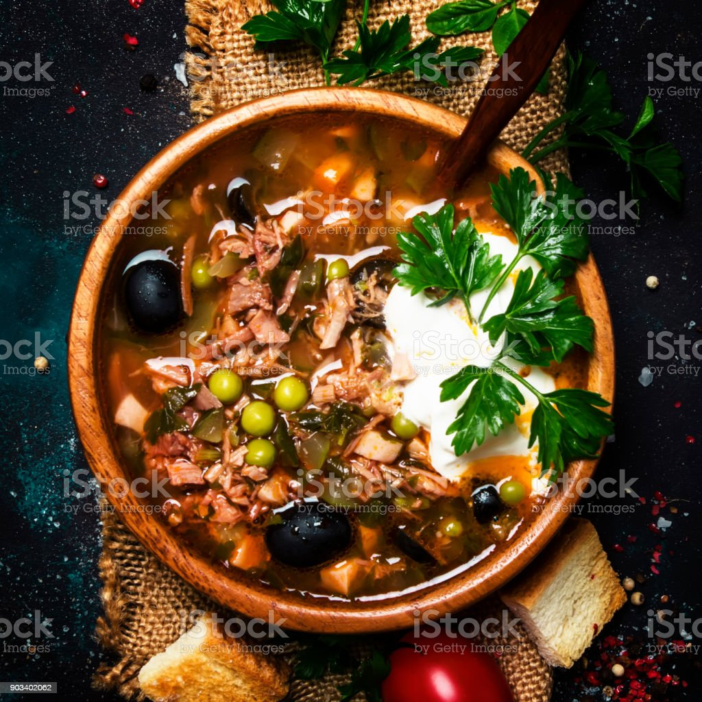 Russian Meat And Vegetable Solyanka Soup with Cream And Parsley In Wooden Bowl stock photo