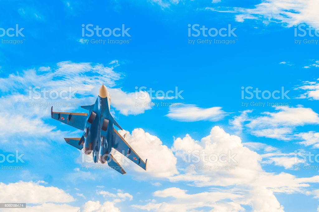 Russian military jet fighter flying in the blue cloudy sky. Background with copy space. stock photo