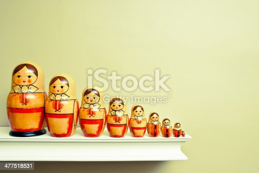 Toned image of a family of Russian nesting dolls all in a row on a ledge