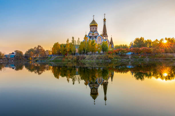 Russian orthodox church known as Church of exaltation of the holy cross and its reflection, at the sunset, in Almaty, Kazakhstan Reflections of Russian Orthodox Church in Almaty, Kazakhstan kazakhstan stock pictures, royalty-free photos & images