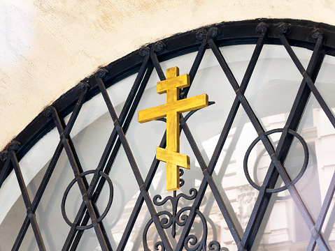 Russian Orthodox wooden cross symbol on a metal gate closeup, detail shot. Eastern Orthodox Christianity religious symbols concept, faith, belief, nobody
