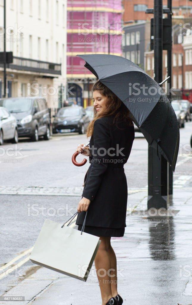 Russian outdoor girl fashion umbrella shopping in rainy Belgravia stock photo