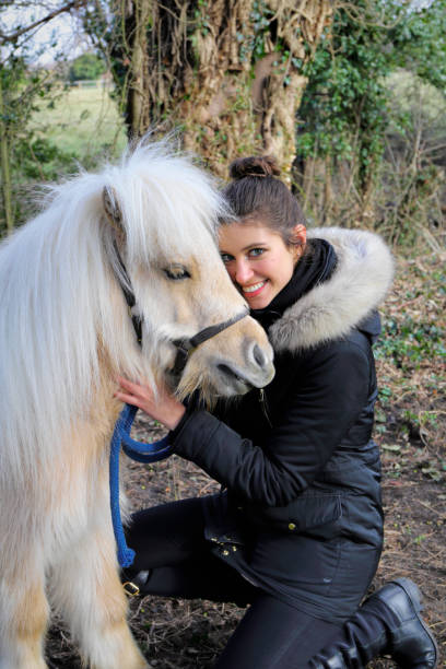 russian outdoor girl hugs white maned palomino miniature shetland pony - whiteway pony stock photos and pictures