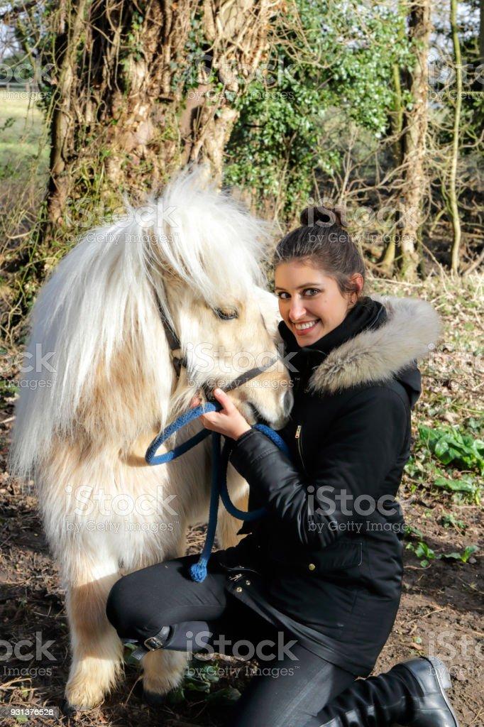 Russian outdoor girl hugs white maned palomino miniature Shetland pony stock photo