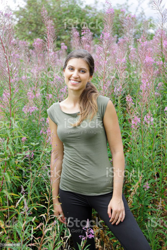 Russian outdoor girl with tall pink flowers fireweed stock photo