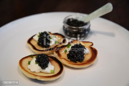 Russian pancakes or blini with sour cream and black sturgeon caviar with a full jar of caviar with a mother-of-pearl spoon on a plate, close up