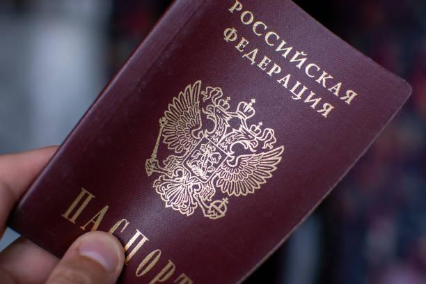 russisch paspoort in de hand - rusland stockfoto's en -beelden