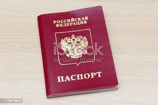 Russian passport on a wooden background. The inscription in Russian: Russian Federation, Passport.