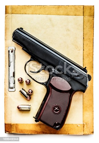 russian pistol with its bullet over home-made booklet on white background