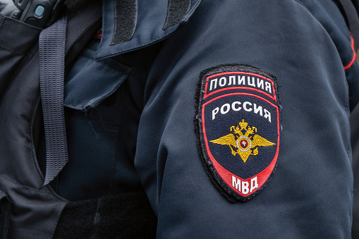 Russian police emblem on the sleeve of a policeman close up