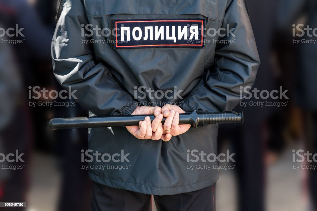 Russian policeman with police truncheon. Text in russian: Police stock photo