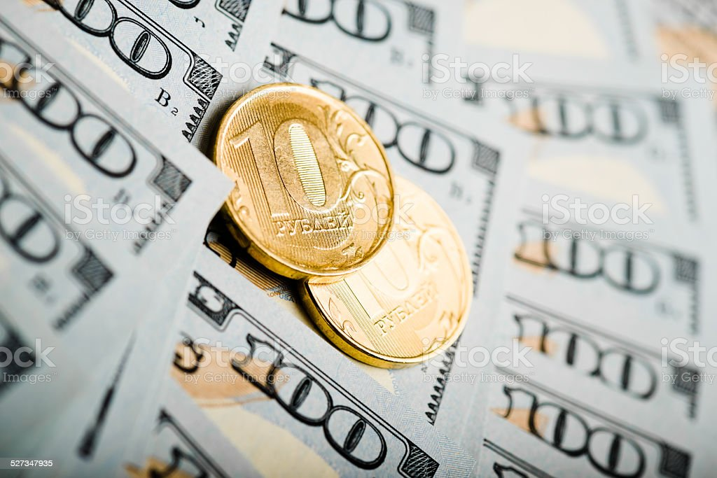 russian roubles coins on banknotes of  dollars stock photo