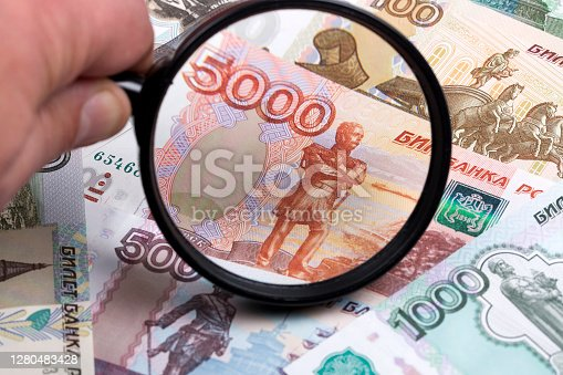Russian ruble in a magnifying glass a business background