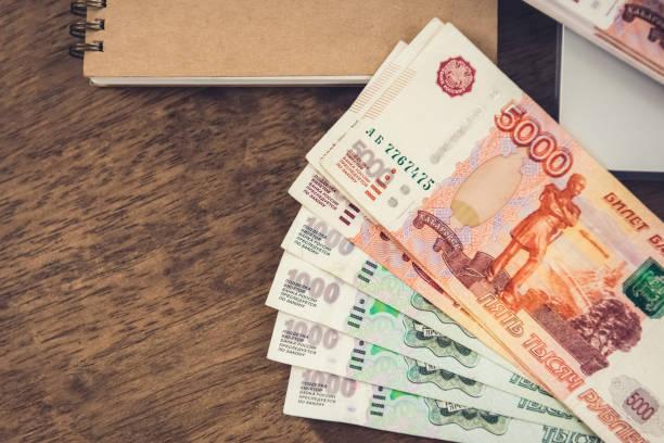 나무 책상에 노트북에 러시아 루블 돈 지폐. - 러시아 루블 뉴스 사진 이미지