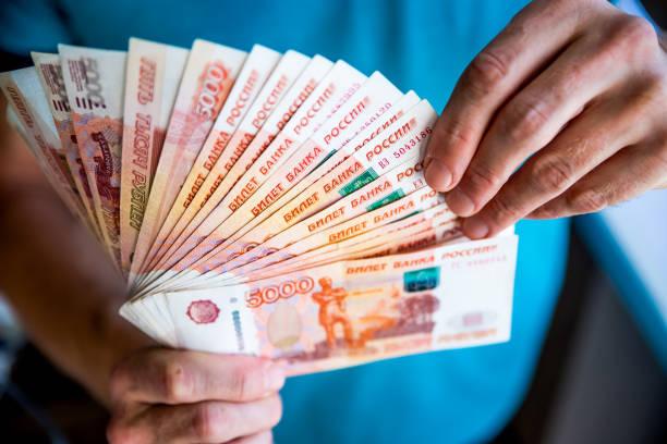 러시아 루블은 fan.male의 손에서 많은 러시아 지폐를 들고 손을. 돈의 양도입니다. 손에서 러시아 루블 명칭의 고립 된 5/1 - 러시아 루블 뉴스 사진 이미지