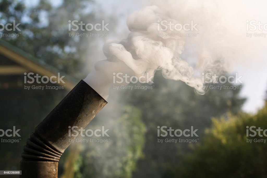 Russian samovar's tube with thick grey and white clouds of smoke stock photo