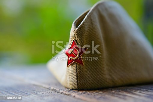 WWII russian soldier cap with red star badge, victory day background