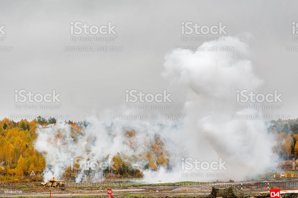 Russian tank T-90 hides in smoke screen from enemy stock photo