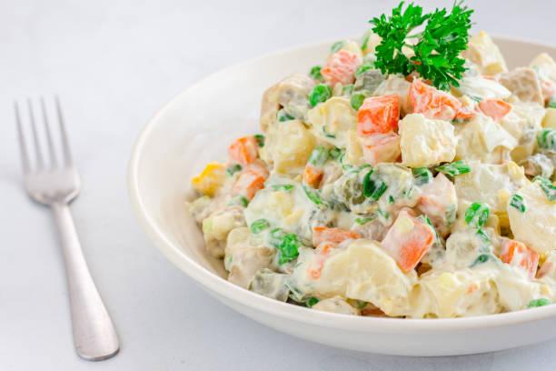 russischer traditioneller salat olivier mit gemüse und fleisch. salat in einer schüssel auf weißem hintergrund - salzkartoffel stock-fotos und bilder