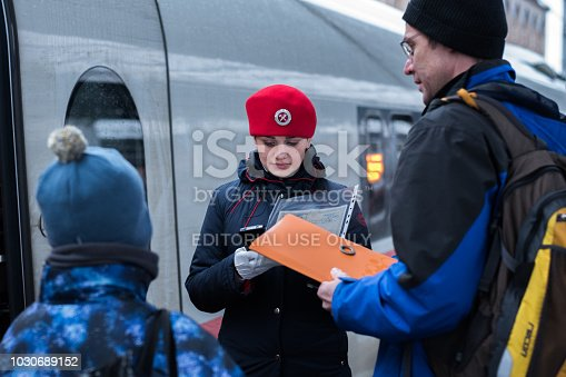 Saint Petersburg, Russia - October 29, 2017: a train conductor in a red beret of a Sapsan express train checks in a passenger with a child using electronic device at Moskovsky railway station.