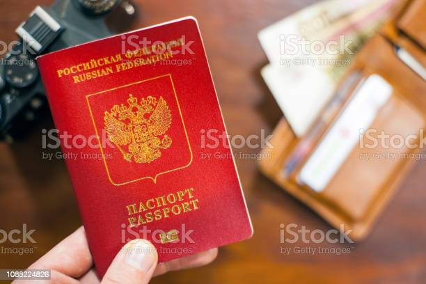 Russian travel passport in hand with wallet and photo camera in the picture id1088224826?b=1&k=6&m=1088224826&s=612x612&h=pl59wwnjt zmwi ipffv oczladbf6i2u tpz7avewu=