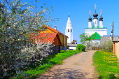 Russian Village old town street at flowerbed springtime - Monastery and churches – Ancient Suzdal typical idyllic russian village, cityscape panorama, Vladimir oblast, Golden Ring, Russia