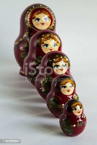 Russian folk wooden toy matryoshka in a Burgundy sundress with an ornament on a white background