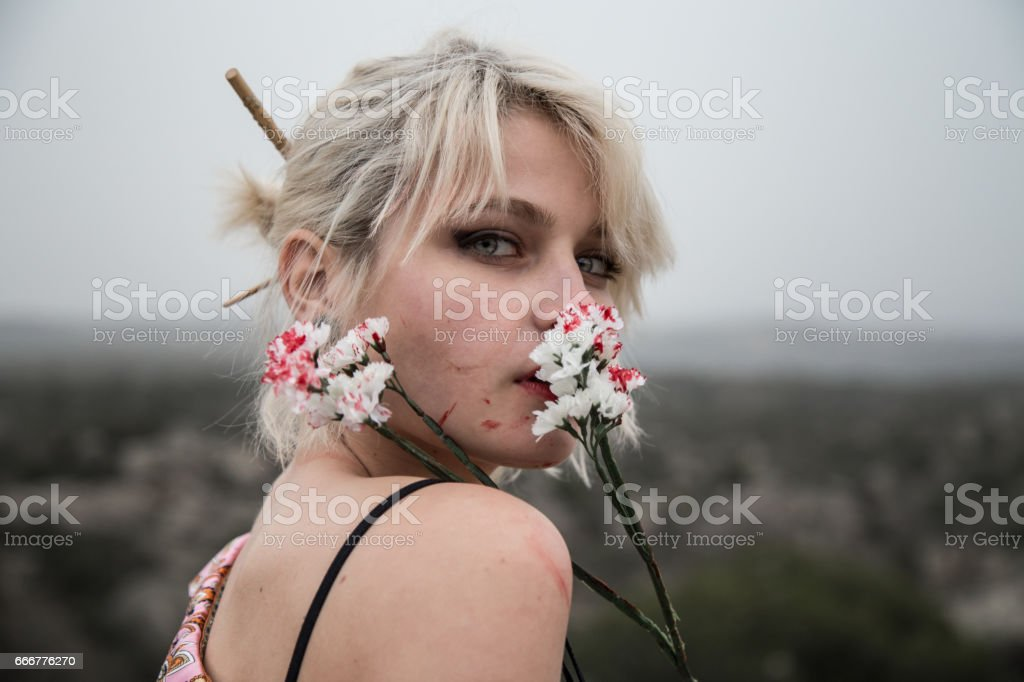 Russian young girl with bloody white flowers in the field. stock photo