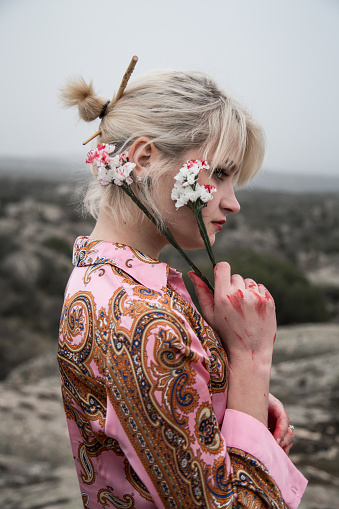 Russian young girl with bloody white flowers in the field.