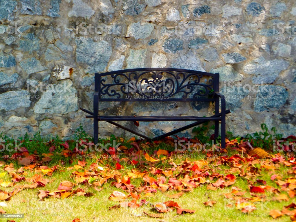 Rust Bench In Garden Granite Stone Wall Stock Photo