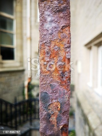 Old wrought iron fence with heavy rust and decay in a vertical format.