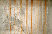 Full-frame weathered concrete wall covered with rust stains.