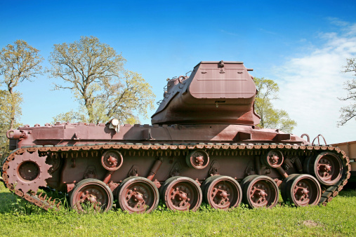 Old World War II American military tank.  It is sitting in the grass, rusting away.