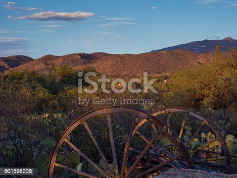 Rusted carriage weels in Arizona desert at sunset - in Tucson, AZ