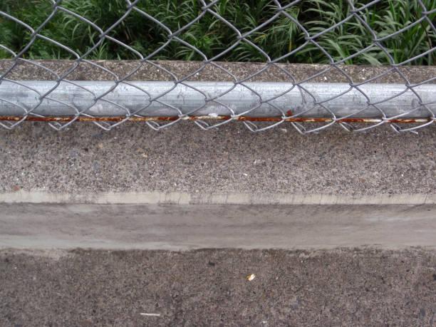 verrostete kettenglied zaun und konkrete bürgersteig seine angeschlossenen - fliesen verlegen stock-fotos und bilder