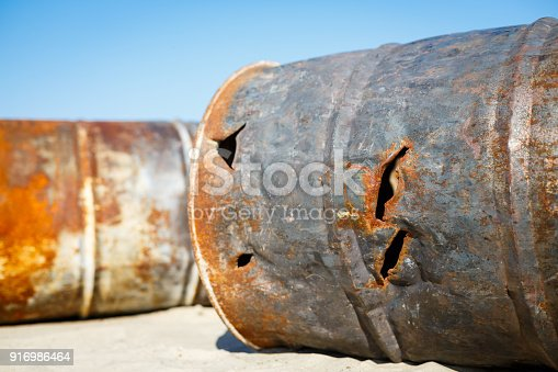 Rusted fuel or chemical barrels left as a trash or waste in a sandy dune. Envitonment and apocalypse concept