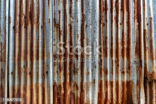 638964834istockphoto Rusted galvanized iron plate, red stain on old metal sheet wall texture. 1190977513