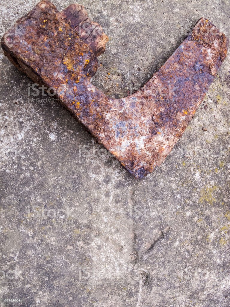 Rusted head of a broken splitting axe lying on a stone surface with a carved arrow on it stock photo