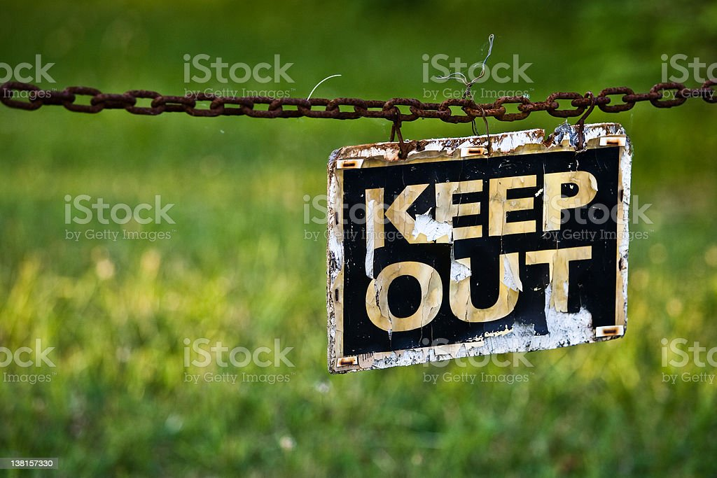 Rusted keep out sign hanging from a chain outside stock photo