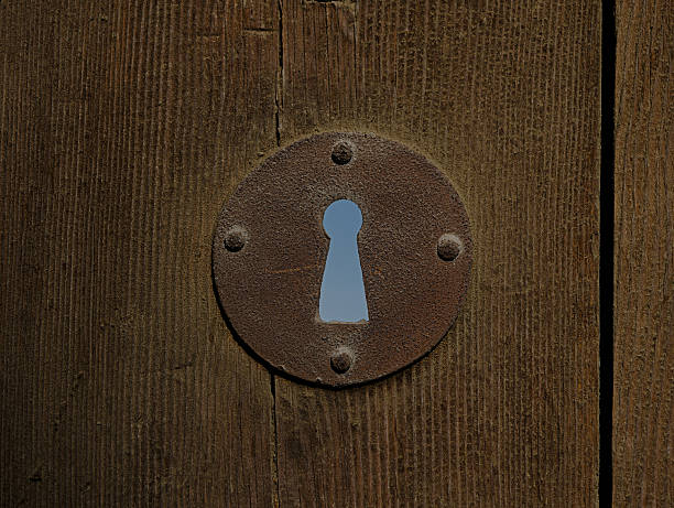 Rusted keyhole of an aged wooden door stock photo