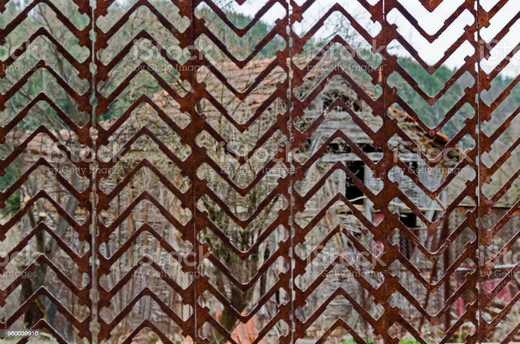 Rusted metal fence section in front of the back yard, Plana mountain stock photo