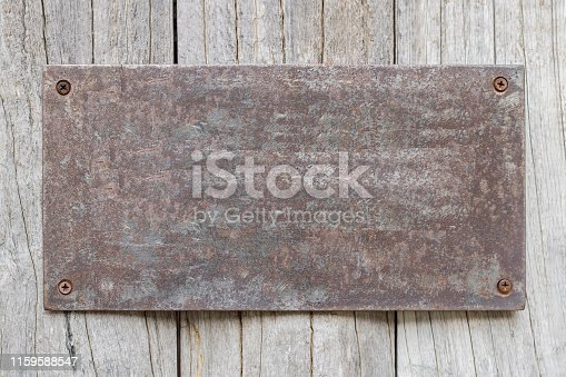 1058533662 istock photo Rusted metal plates on the old wooden background 1159588547