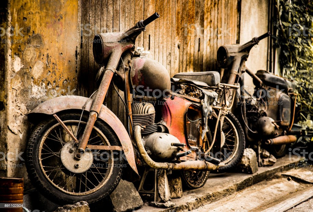 Rusted motorcycle against a grunge wall stock photo
